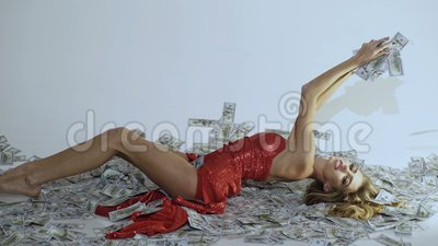 Woman in red dress lying on money. Banknote. Business concept. Easy money. Digital money concept. Finance. Girl in red. Dress. Fashion. Beauty. Business. Make stock video