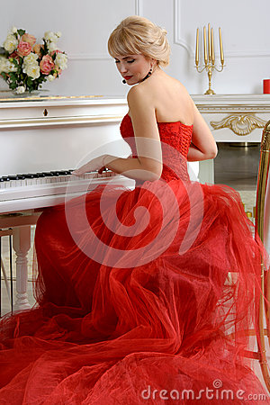 woman red dress playing piano dressed evening gown long train sits white looking slightly to side against 52760388 How to Be an unbelievable Asian Star of the event