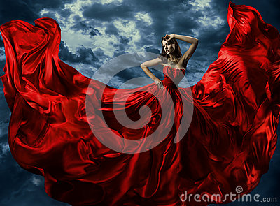 Woman in red evening dress, waving gown with flying long fabric