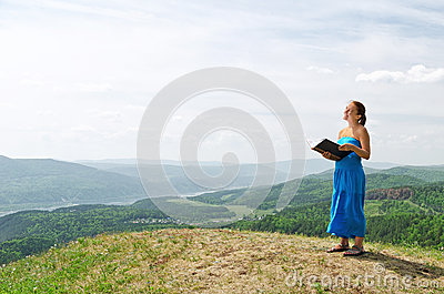 Red haired woman with book on the hilltop