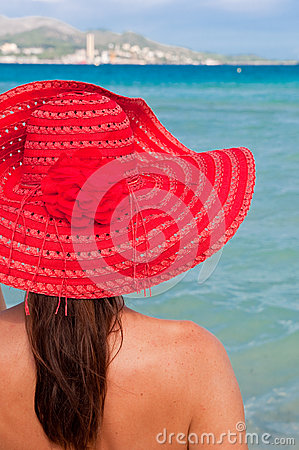 Woman with red hat looking at the sea