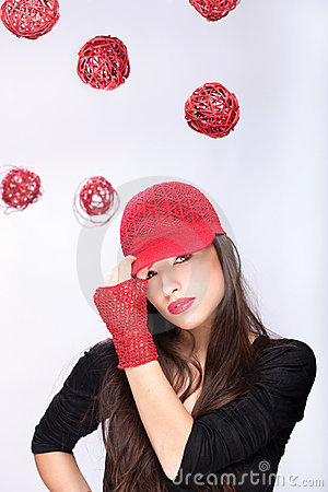Woman with red hat between red balls