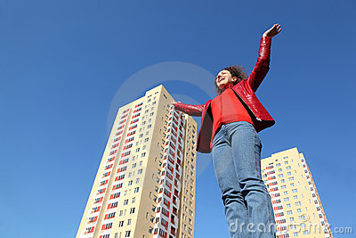 Woman in red jacket and blue jeans raises his hand