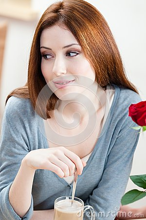 Woman with red rose at the cafe