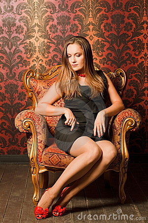 Woman in red shoes and dress sitting on chair