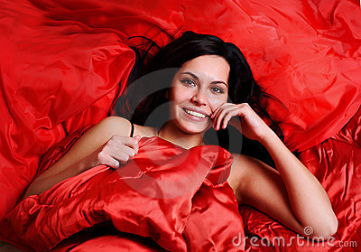 Woman on red silk sheets