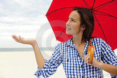 Woman with red umbrella touching the rain