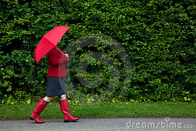 Woman in red walking with umbrella