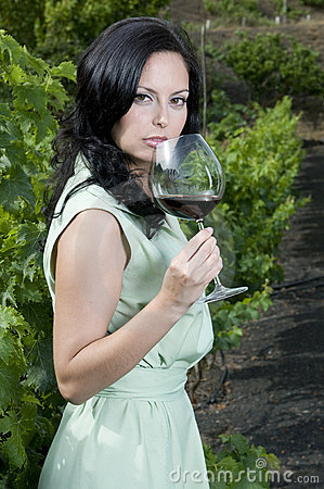 Woman with red wine glass in a vineyard