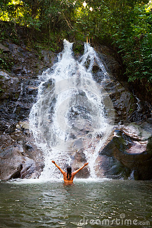 Woman refreshing herself in beautiful waterfall