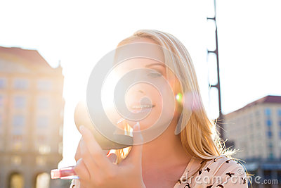 Woman refreshing makeup with gloss in the sun