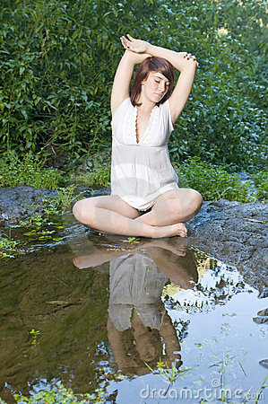 Woman in relax position near a pond