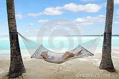 Happy woman relaxing on hammock on the beach during travel vacation on