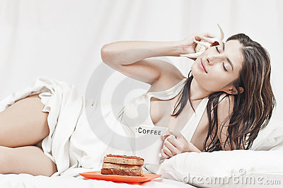 Woman relaxing on bed with a cake and a shell