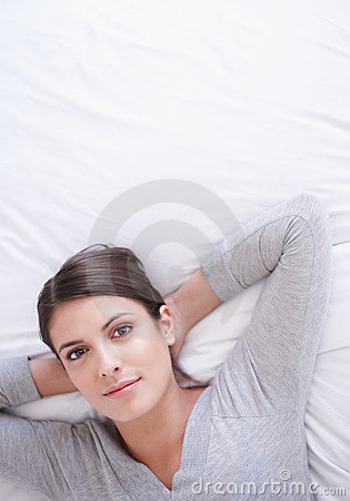 Woman relaxing on bed with hands behind head