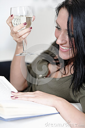 Woman relaxing with a book and wine