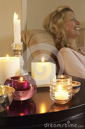 Free Woman Relaxing By Table With Lit Candles Royalty Free Stock Photo - 31831165