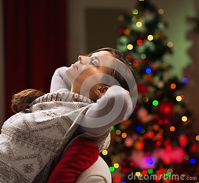 Woman relaxing on chair in front of Christmas tree