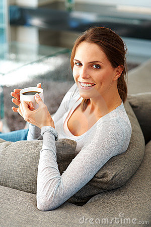 Woman relaxing on couch with cup of coffee