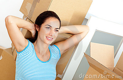 Woman relaxing on the floor after unpacking boxes