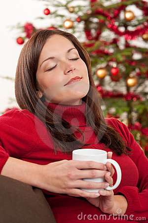 Woman relaxing in front of Christmas tree
