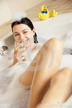 Woman Relaxing With Glass Of Wine In Bath