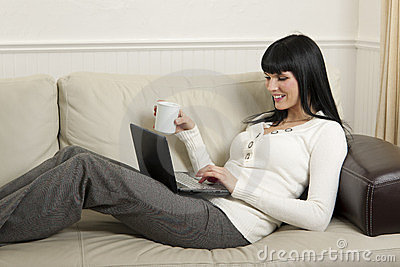 Woman  relaxing at home with her computer
