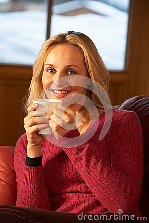 Woman Relaxing With Hot Drink On Sofa Watching TV