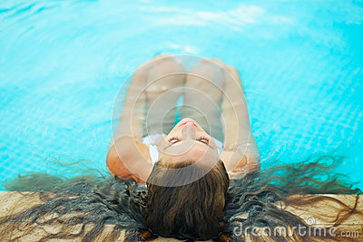 Woman relaxing in pool. Rear view