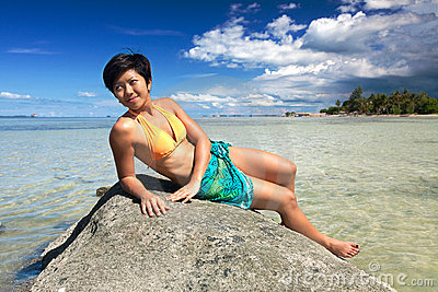 Woman relaxing on a rock by a tropical beach