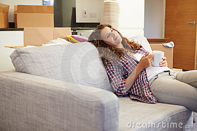 Woman Relaxing On Sofa With Hot Drink In New Home