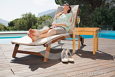Woman relaxing on sun lounger by swimming pool