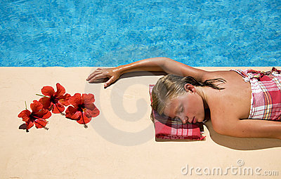 Woman relaxing at the swimming pool side