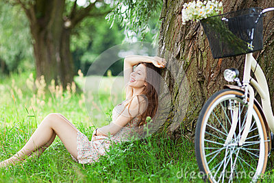 Woman relaxing under a tree next to a bicycle