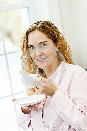 Woman relaxing by the window with beverage