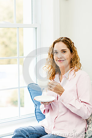 Woman relaxing by the window with coffee