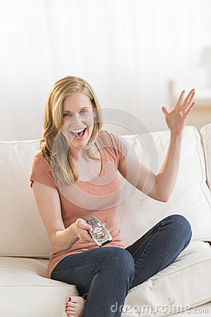 Woman With Remote Control Watching TV On Sofa