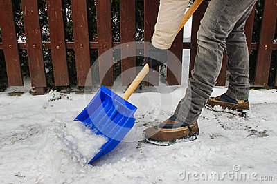 Woman removing snow from the sidewalk