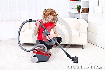 Woman repairs vacuum cleaner