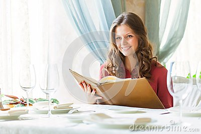 A woman in a restaurant with the menu in hands