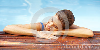 Woman resting at edge of pool