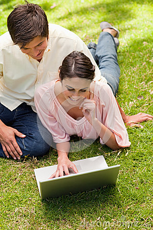 Woman resting her face against her hand while using a laptop wit