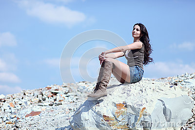 Woman resting on stone boulder