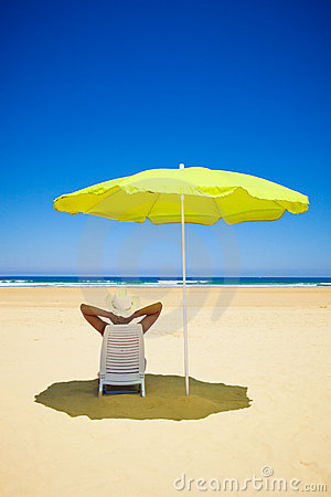 Woman resting under a beach umbrella
