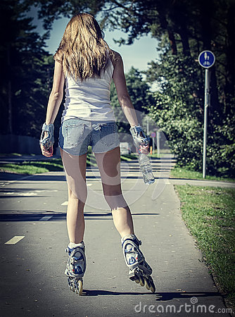 Woman ride rollerblades in the park. Back view.