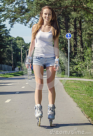 Woman ride rollerblades in the park.