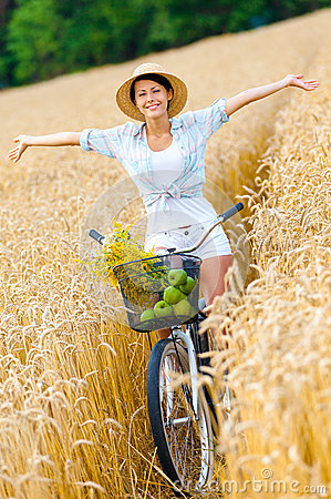Free Woman Rides Bicycle With Apples And Flowers In Rye Royalty Free Stock Photography - 39060797