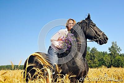 Woman rides pretty black horse in field