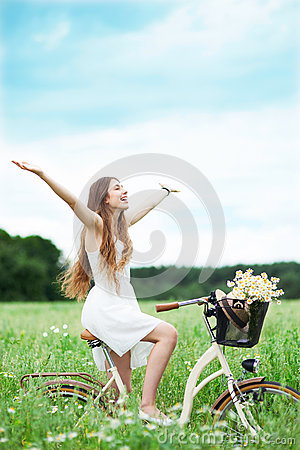 Woman riding bicycle in wildflower field