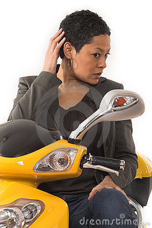 Woman riding electric scooter with no helmet